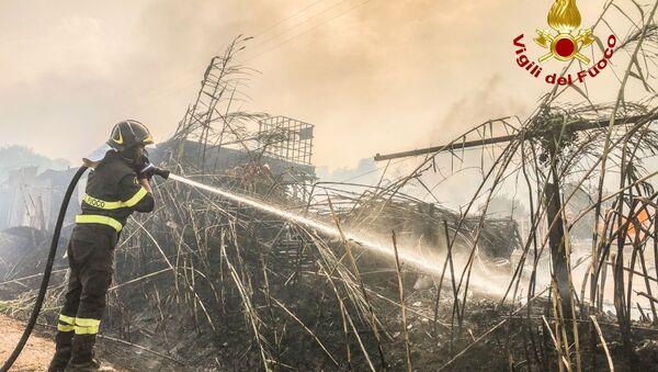 A firefighter battles the flames after a large wildfire broke out near Santu Lussurgiu, Sardinia, Italy July 24, 2021. - Sputnik International