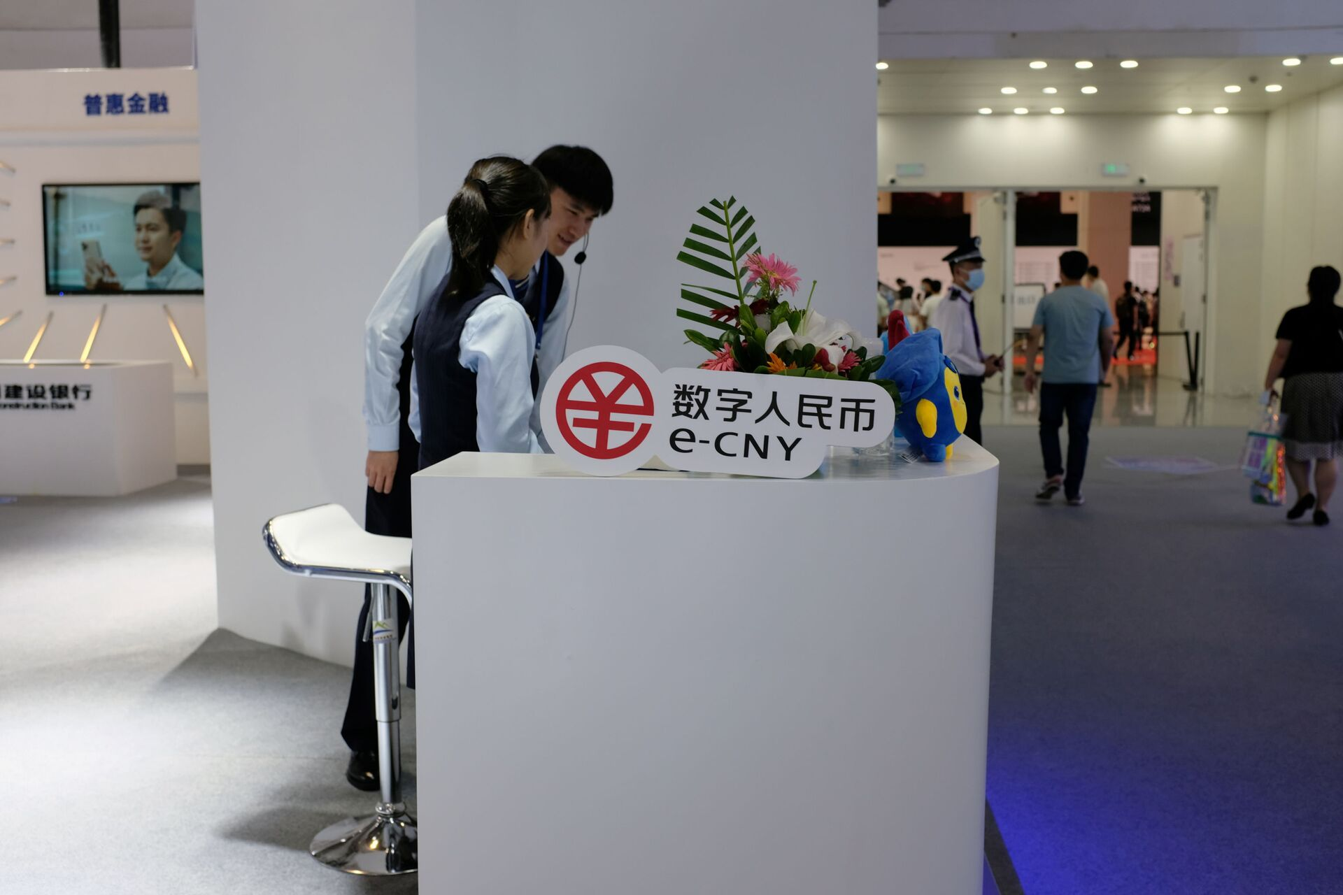 Staff members stand next to a sign of China's digital yuan, or e-CNY, at the World Artificial Intelligence Conference (WAIC) in Shanghai, China July 8, 2021. - Sputnik International, 1920, 07.09.2021