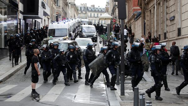 Police forces walk on the Champs Elysees Avenue after clashes on the sidelines of a demonstration against France's restrictions to fight the coronavirus disease (COVID-19) outbreak, in Paris, France, July 24, 2021.  - Sputnik International