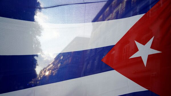 The silhouette of the city is seen through a Cuban flag during a protest against the  U.S. economic embargo in Cuba - Sputnik International