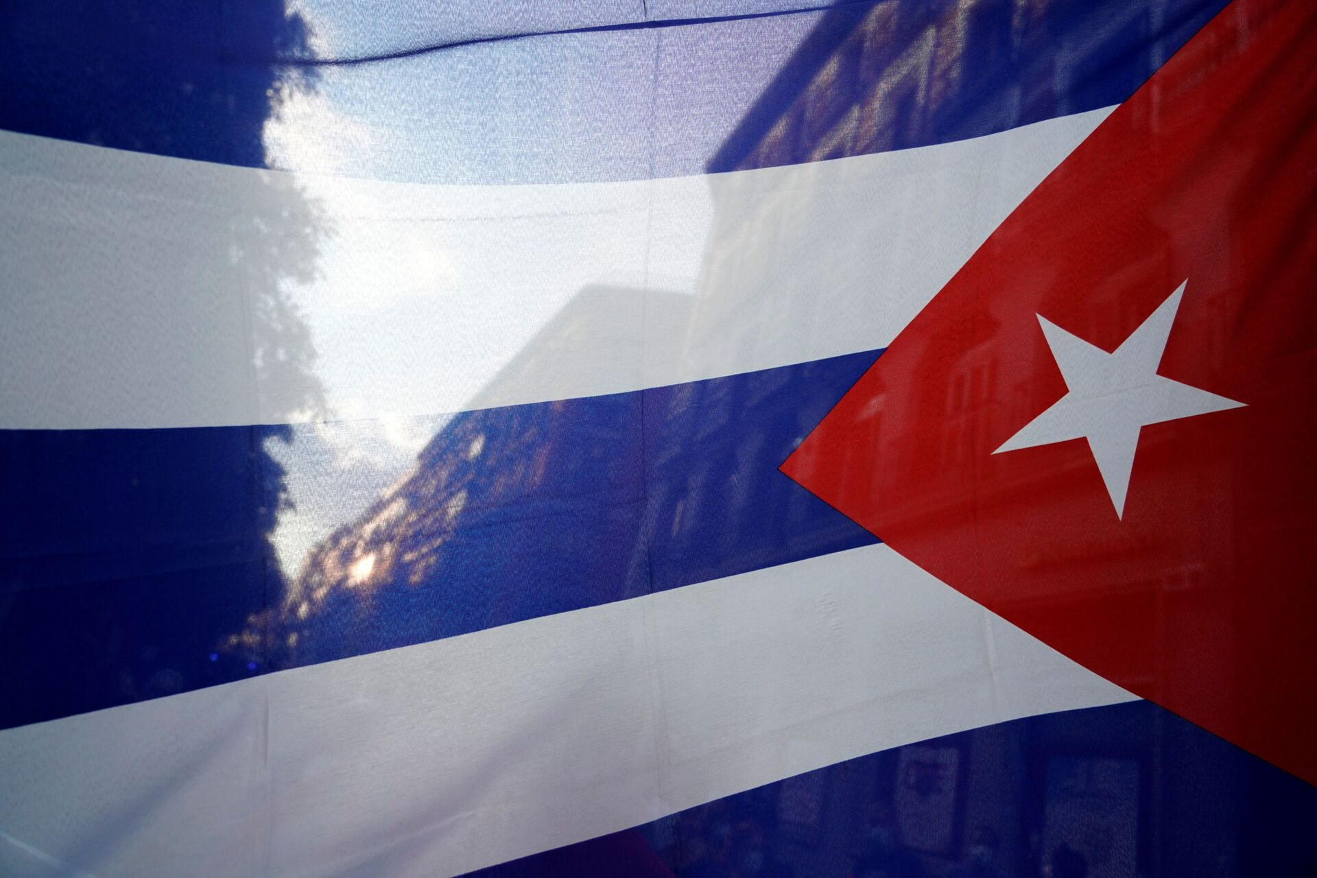 The silhouette of the city is seen through a Cuban flag during a protest against the  U.S. economic embargo in Cuba - Sputnik International, 1920, 07.09.2021