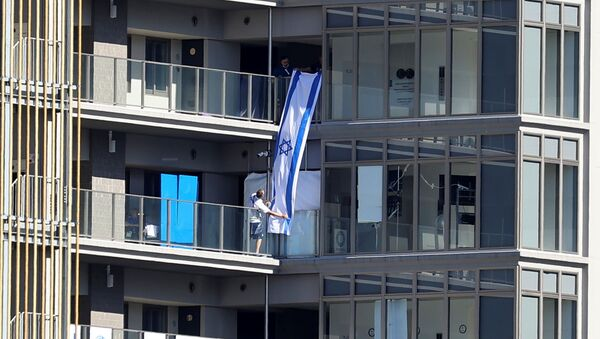 People hang an Israeli flag at the Athletes Village, where a person has tested positive for COVID-19, ahead of Tokyo 2020 Olympic Games in Tokyo, Japan July 17,  2021 - Sputnik International