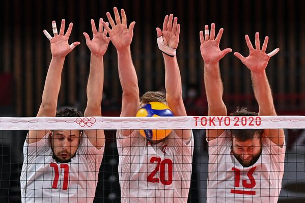 Poland's Fabian Drzyzga, Mateusz Bieniek, and Michal Kubiak attempt to block a shot in the men's preliminary round pool A volleyball match between Poland and Venezuela during the Tokyo 2020 Olympic Games at Ariake Arena. - Sputnik International