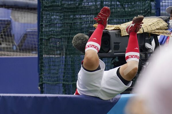 Yu Yamamoto of Japan falls over a wall after reaching for a foul ball hit by American Amanda Chidester in the sixth inning of a softball game at the Tokyo 2020 Olympics. - Sputnik International