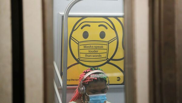 A commuter wears a mask under public safety signage as cases of the infectious coronavirus Delta variant continue to rise in New York City, New York, U.S., July 26, 2021. REUTERS/Andrew Kelly - Sputnik International