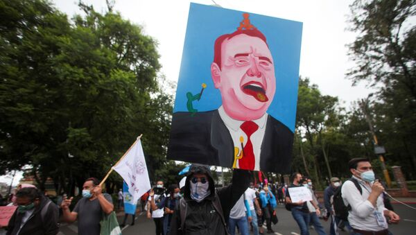 A demonstrator holds up a painting of Guatemalan President Alejandro Giammattei during a protest to demand the resignation of Giammattei and Attorney General Maria Porras, in Guatemala City, Guatemala July 29, 2021 - Sputnik International