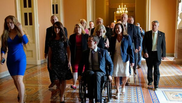 House Republicans, including Representatives Lauren Boebert (R-CO), Kat Cammack (R-FL), Madison Cawthorn (R-NC), Marjorie Taylor Greene (R-GA), Lisa McClain (R-MI) and Jody Hice (R-GA), who oppose mask mandates march as a group to the Senate chamber to highlight different coronavirus disease (COVID-19) mask rules between the House and Senate sides of the U.S. Capitol in Washington, U.S., July 29, 2021.  - Sputnik International