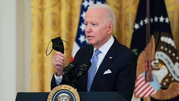 U.S. President Joe Biden holds his mask as he speaks about the pace of coronavirus disease (COVID-19) vaccinations in the United States during remarks in the East Room of the White House in Washington, U.S., July 29, 2021 - Sputnik International