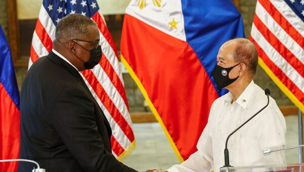 United States Defense Secretary Lloyd Austin (L) and Philippines' Defense Secretary Delfin Lorenzana (R) shake hands after a bilateral meeting at Camp Aguinaldo military camp in Quezon City, Metro Manila, Philippines, July 30, 2021.  - Sputnik International