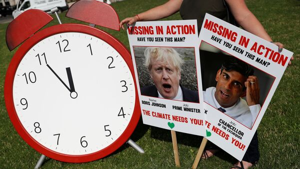 A protester from the Climate Coalition demonstrates, with 100 hundred days to go before the start of the COP26 climate summit, in Parliament Square, London, Britain, July 23, 2021.  REUTERS/Peter Nicholls - Sputnik International