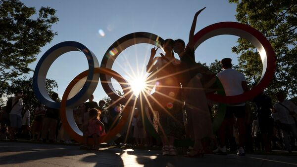 People pose for a photograph in front of an Olympic rings monument outside the National Stadium, the main stadium of Tokyo 2020 Olympic and Paralympic Games, amid the coronavirus disease (COVID-19) pandemic, in Tokyo, Japan July 31, 2021.  REUTERS/Issei Kato - Sputnik International