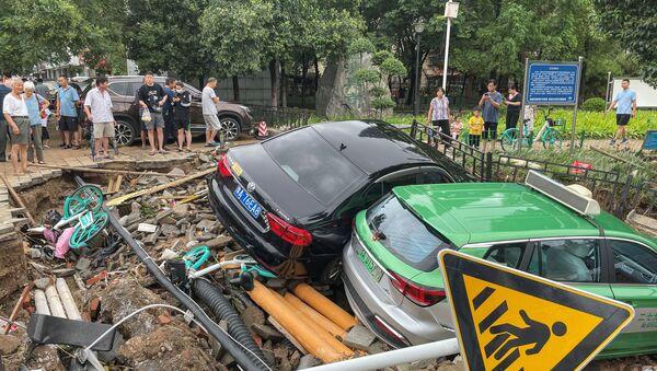Damaged cars rest on debris after heavy rains hit the city of Zhengzhou causing floods in China's central Henan province on July 21, 2021.  - Sputnik International