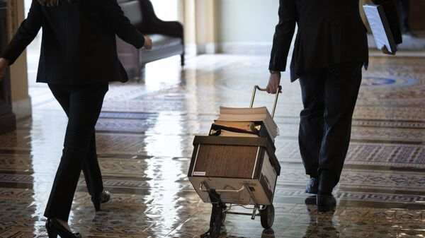 Documents, including text of the bipartisan infrastructure legislation, is wheeled toward the office of Senate Majority Leader Chuck Schumer (D-NY) at the U.S. Capitol on August 2, 2021 in Washington, DC. - Sputnik International