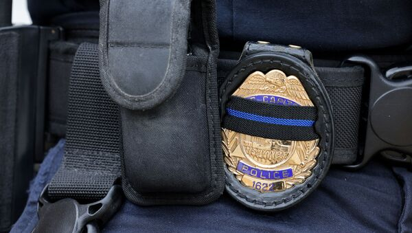 A U.S. Capitol police officer's badge shows a black stripe in honor of deceased colleagues as he guards the building on Capitol Hill in Washington, May 28, 2021. REUTERS/Evelyn Hockstein/File Photo - Sputnik International