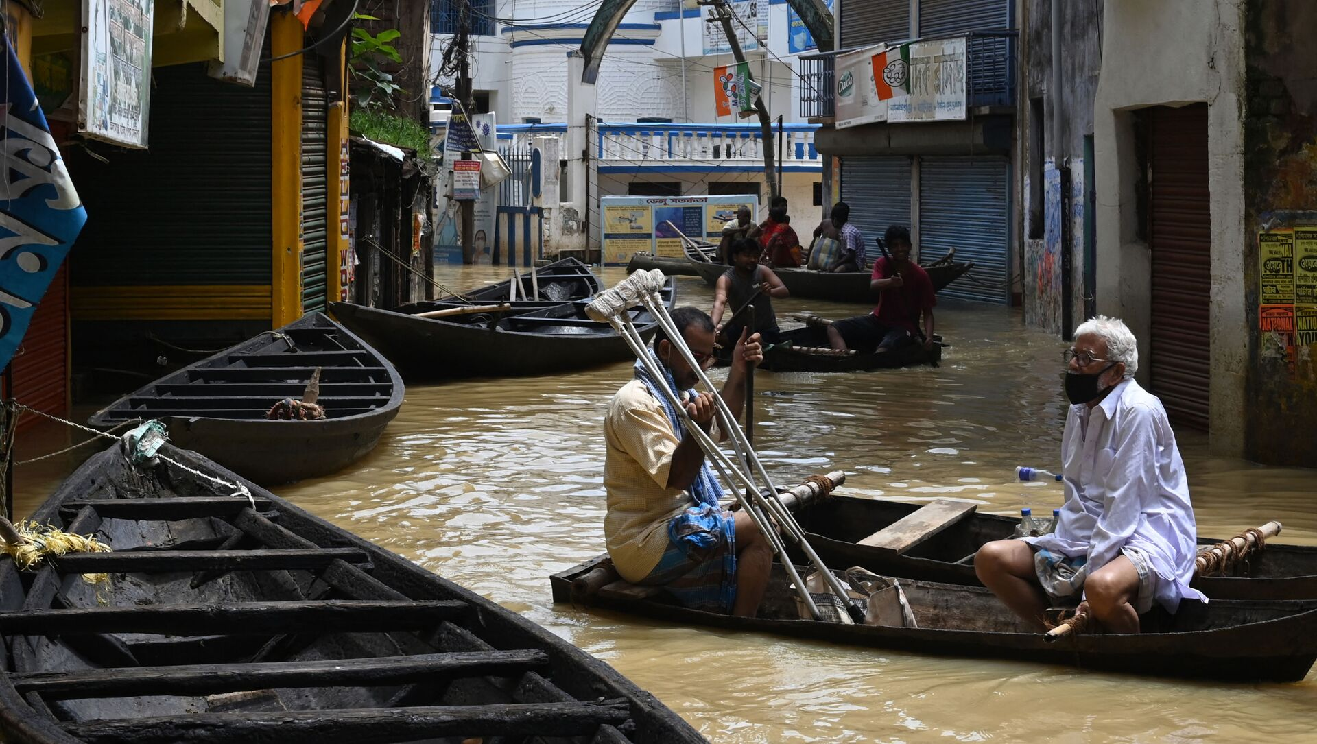 Residents ride a boat over a road submerged by floodwaters following heavy monsoon rains in Ghatal, Paschim Medinipur district, about 100 km from Kolkata on August 2, 2021.  - Sputnik International, 1920, 03.08.2021