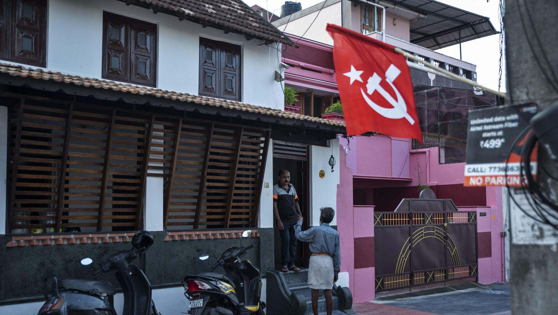 A man talks to his neighbor as a Communist Party of India (Marxist) flag is displayed as part of election campaign at a street inhabited by members of the Tamil Brahmin community in Thiruvanathapuram, Kerala state, India, Saturday, April 3, 2021.  - Sputnik International, 1920, 03.08.2021