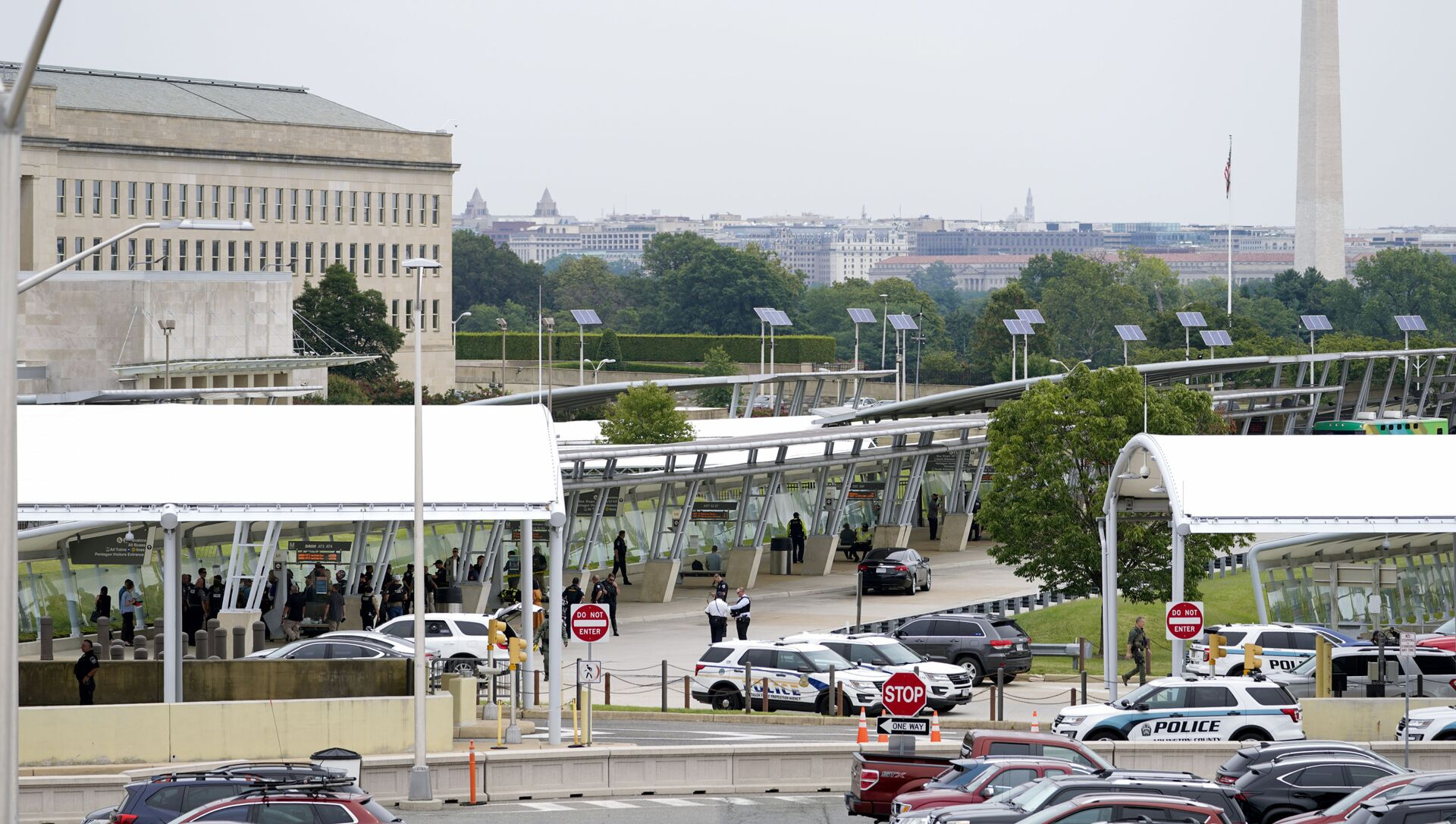 With the Washington Monument in the background, police vehicles are seen outside the Pentagon Metro area Tuesday, Aug. 3, 2021, at the Pentagon in Washington. The Pentagon is on lockdown after multiple gunshots were fired near a platform by the facility's Metro station. - Sputnik International, 1920, 04.08.2021