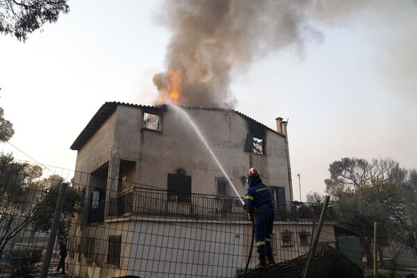 A firefighter tries to extinguish the flames at a burning house in the Varibobi area, northern Athens, Greece, Wednesday, 4 August 2021.  - Sputnik International