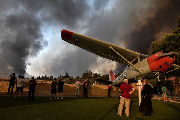 People gather at the entrance to a military airport in Tatoi near Acharnes during a massive forest fire, north of Athens on 3 August 2021. - Sputnik International