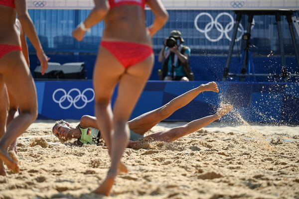 Germany's Laura Ludwig falls on the sand while reaching for a shot in the women's preliminary beach volleyball pool F match between Switzerland and Germany. - Sputnik International
