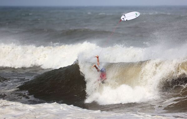 Gabriel Medina of Brazil in action as he falls into the sea with his surfboard seen above him. - Sputnik International