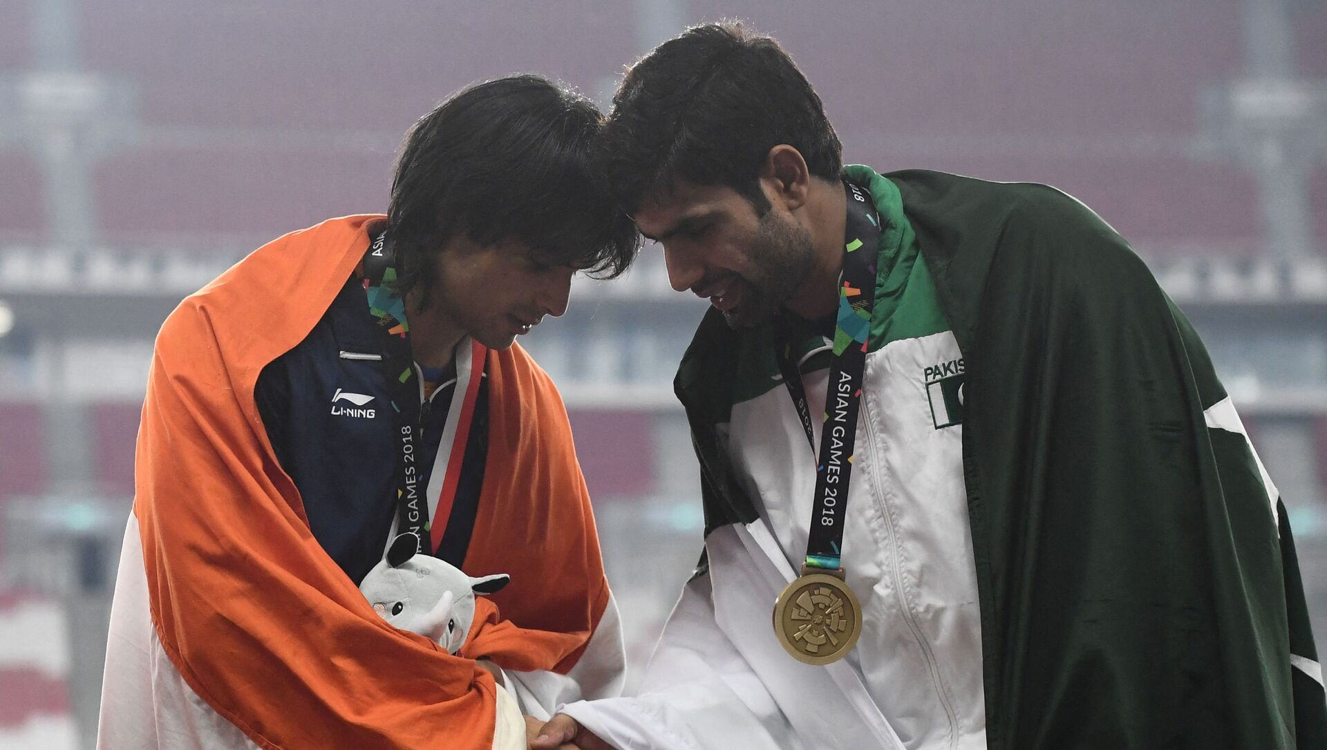 Gold medallist India's Neeraj Chopra (L) shakes hands with bronze medallist Pakistan's Arshad Nadeem during the victory ceremony for the men's javelin throw athletics event during the 2018 Asian Games in Jakarta on August 27, 2018.  - Sputnik International, 1920, 04.08.2021