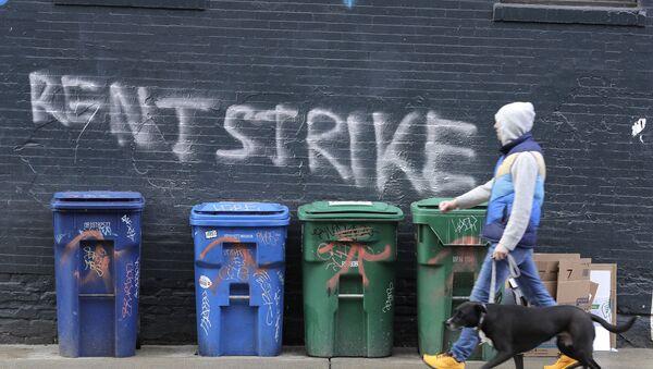 A pedestrian walks past graffiti that reads Rent Strike Wednesday, April 1, 2020, in Seattle's Capitol Hill neighborhood.  - Sputnik International