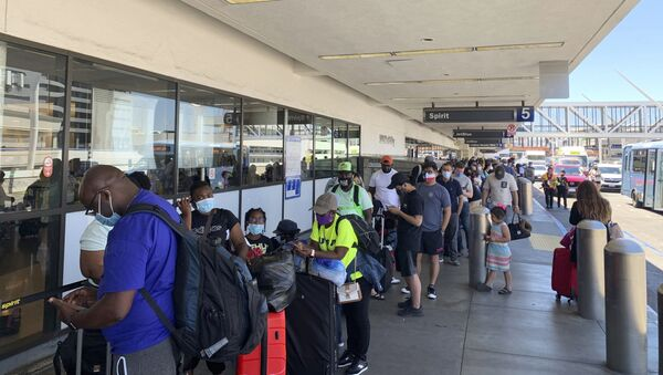 Passengers line up outside the Spirit Airlines terminal at Los Angeles International Airport in Los Angeles on Tuesday, Aug. 3, 2021. Spirit Airlines canceled more than half its schedule Tuesday, and American Airlines struggled to recover from weekend storms at its Texas home, stranding thousands of passengers at the height of the summer travel season. - Sputnik International
