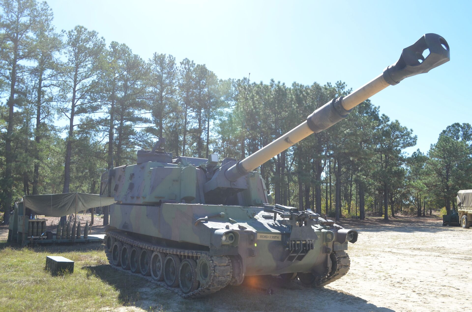 """The M109 Paladin Self-Propelled Howitzer standing ready deep in the southern training areas at Fort Bragg. Nine National Guard troops from North and South Carolina, Florida, Georgia, Mississippi, Illinois and New Jersey are attending the 13 Bravo artillery military occupational specialty (MOS) reclassification course and will learn how to be a crew member on the three main """"cannon"""" artillery weapons systems in the U.S. Army: The M119A3 105mm light towed howitzer, M777A2 155mm medium towed howitzer and the M109A6 Paladin 155mm self-propelled howitzer. Over the course of two days in the field, students will fire hundreds of rounds from all three weapons. - Sputnik International, 1920, 07.09.2021"""