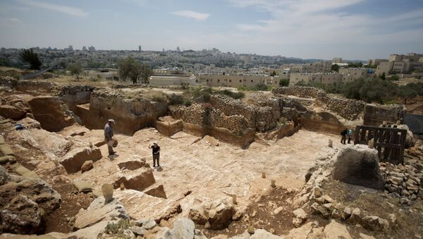 Israeli Antiquities Authority archaeologists work at the excavation site of a 2,000-year-old stone quarry dating back to the Second Temple period discovered in Jerusalem on May 8, 2013 before the construction of a new road in the northern part of city. - Sputnik International