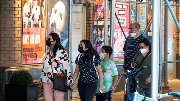 People walk near posters of theatre shows while they wear masks to prevent against the spread of the coronavirus disease (COVID-19), as the highly transmissible Delta variant has led to a surge in infections, in New York City, U.S - Sputnik International