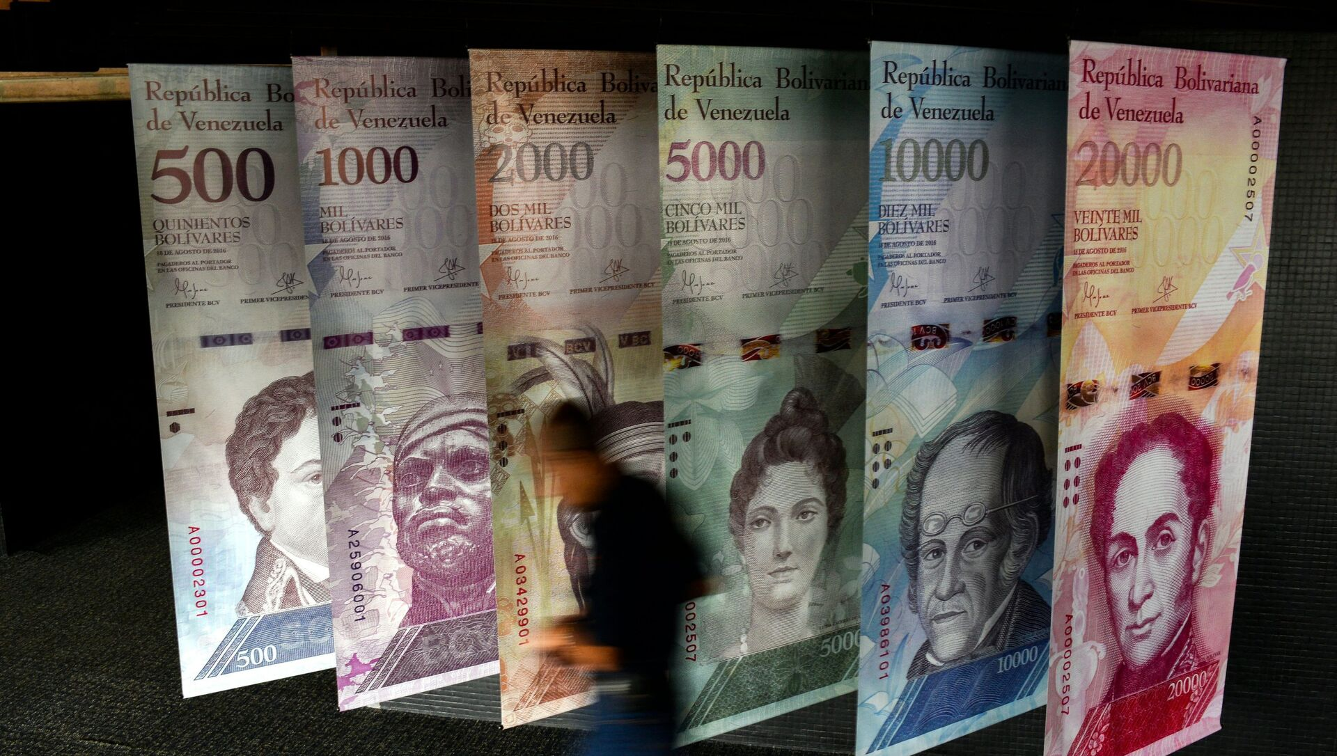 A man walks past banners showing banners depicting Venezuela's currency, the Bolivar, at the Central Bank of Venezuela (BCV) in Caracas on January 31, 2018.  - Sputnik International, 1920, 05.08.2021