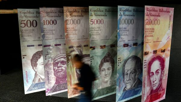 A man walks past banners showing banners depicting Venezuela's currency, the Bolivar, at the Central Bank of Venezuela (BCV) in Caracas on January 31, 2018.  - Sputnik International