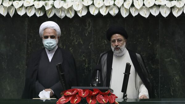 President Ebrahim Raisi, right, takes his oath as president, as Judiciary Chief Gholamhossein Mohseni Ejehi listens in a ceremony at the parliament in Tehran, Iran, Thursday, Aug. 5, 2021.  - Sputnik International