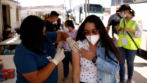 A Mexican woman receives a dose of the Johnson & Johnson coronavirus disease (COVID-19) vaccine, during a binational vaccination program, at the Tornillo-Guadalupe international bridge, in Tornillo, Texas, U.S., July 28, 2021 - Sputnik International
