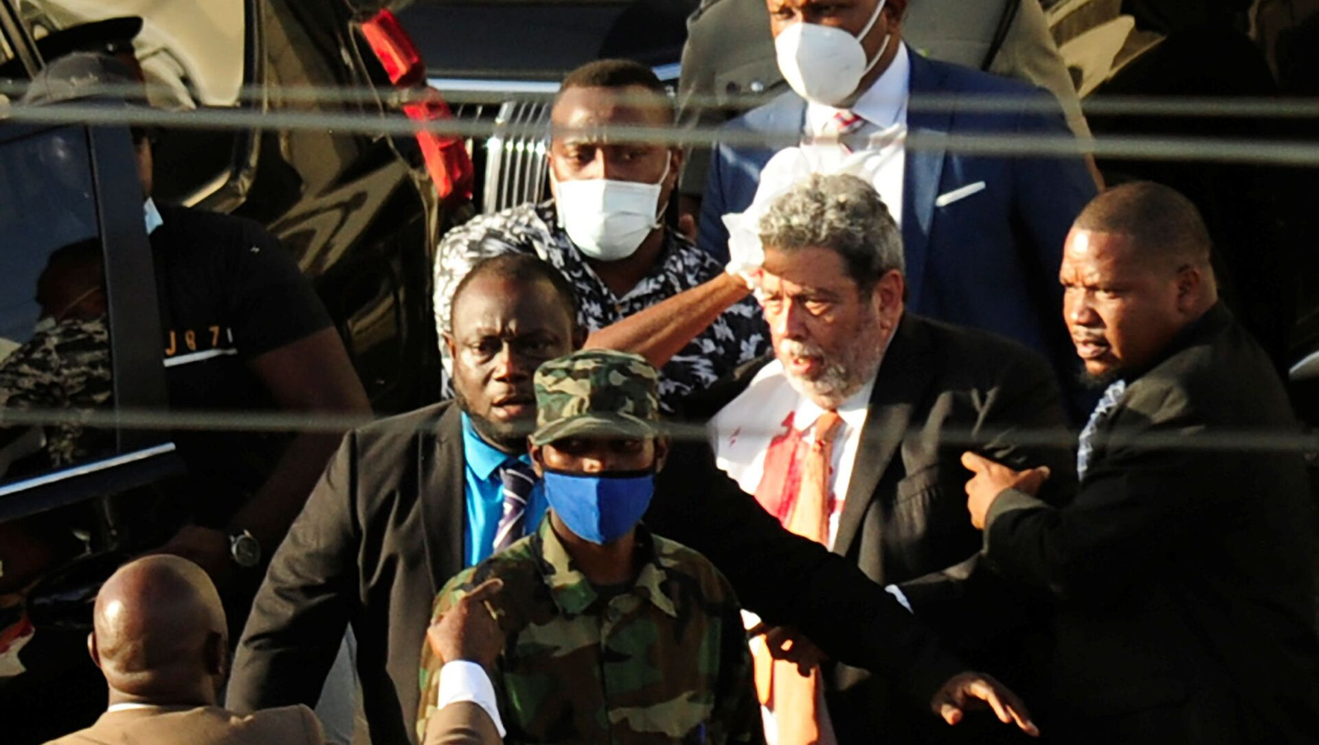 St. Vincent and the Grenadines Prime Minister Ralph Gonsalves, his shirt covered in blood, is evacuated after media reported that he was hit by a stone during a protest in Kingstown, St. Vincent and the Grenadines August 5, 2021.  - Sputnik International, 1920, 06.08.2021