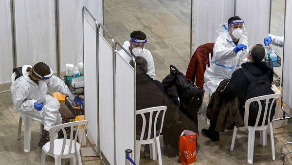 Swab samples for COVID-24 coronavirus disease testing are taken by medics from travellers upon arrival at the rapid testing centre in Israel's Ben-Gurion International Airport in Lod, near Tel Aviv, on January 24, 2021.  - Sputnik International