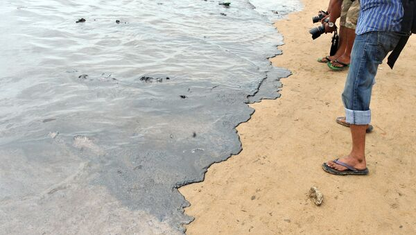 Photographers take pictures of oil contaminated water on the shores of Juhu Chowpatty beach in Mumbai on August 7, 2011.  - Sputnik International
