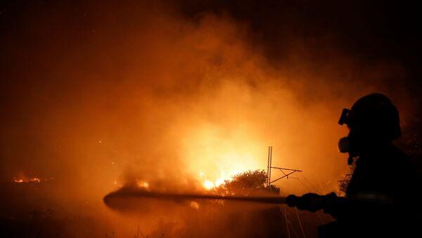 A firefighter battles a wildfire near Afidnes, north of Athens, Greece August 5, 2021.  - Sputnik International