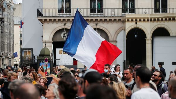 Protesters hold a French flag during a demonstration called by the yellow vests (gilets jaunes) movement against France's restrictions, including a compulsory health pass, to fight the coronavirus disease (COVID-19) outbreak in Paris, France, August 5, 2021. - Sputnik International