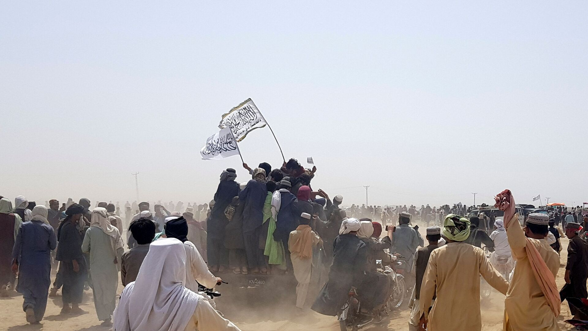 People standing on a vehicle hold Taliban flags as people gather near the Friendship Gate crossing point in the Pakistan-Afghanistan border town of Chaman, Pakistan July 14, 2021. Picture taken July 14, 2021. - Sputnik International, 1920, 07.09.2021