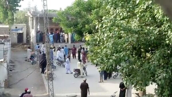 People gather outside a Hindu temple that was set on fire by an angry mob after reports that a Hindu boy had urinated in the library of an Islamic seminary, in Bhong, Pakistan August 4, 2021 in this screen grab from a social media video - Sputnik International