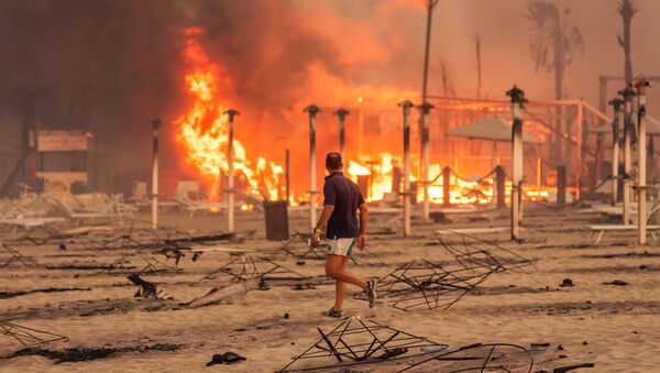 A man walks in front of a fire at Le Capannine beach in Catania, Sicily, Italy, July 30, 2021, in this photo obtained from social media on July 31, 2021 - Sputnik International