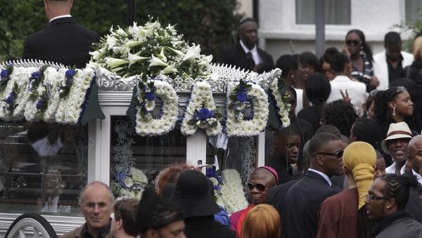 People gather around a hearse carrying Mark Duggan's coffin, as it prepares to leave the church for the cemetery during the funeral procession in north London,  Friday, Sept. 9, 2011. - Sputnik International