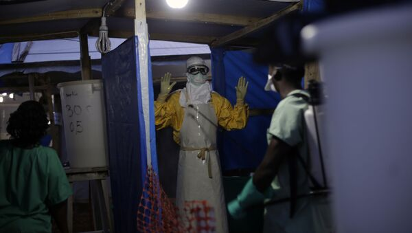 FILE- In this Nov. 20, 2014 file photo, an MSF Ebola heath worker is sprayed as he leaves the contaminated zone at the Ebola treatment centre in Gueckedou, Guinea - Sputnik International