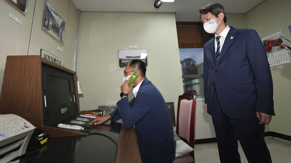 A South Korean government official makes a phone calls to North Korea via the dedicated communications hotline as South Korean Unification Minister Lee In-young, right, watches during a visit to Panmunjom in the Demilitarized Zone, South Korea, Wednesday, Sept. 16, 2020 - Sputnik International