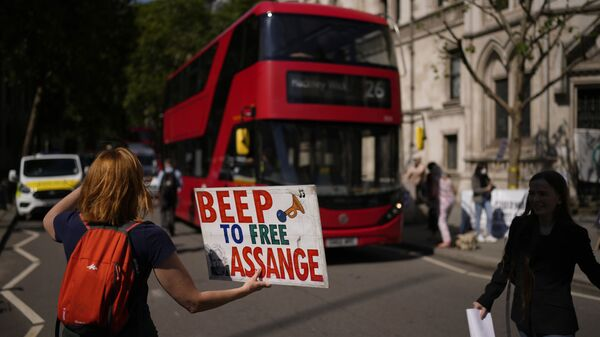 A supporter of WikiLeaks founder Julian Assange holds a placard as they protest, during the first hearing in the Julian Assange extradition appeal, at the High Court in London, Wednesday, Aug. 11, 2021. - Sputnik International