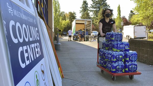 A volunteer helps set up snacks at a cooling center established to help vulnerable residents ride out the second dangerous heat wave to grip the Pacific Northwest this summer, on Wednesday, Aug. 11, 2021. - Sputnik International