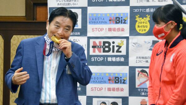 FILE PHOTO: Nagoya city Mayor Takashi Kawamura bites the Tokyo 2020 Olympic Games gold medal of the softball athlete Miu Goto during a ceremony in Nagoya, central Japan, 4 August 2021, in this photo taken by Kyodo.  - Sputnik International