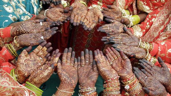 Brides show henna art on their palms as they pose for photographs during a Muslim mass marriage in Ahmadabad, India on Sunday, 21 March 2010. - Sputnik International